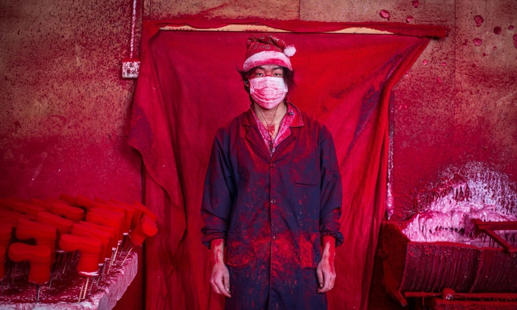Santa's workshop … 19-year-old Wei works in a factory in Yiwu, China, coating polystyrene snowflakes with red powder. Inside the 'Christmas village' of Yiwu, there's no snow and no elves, just 600 factories that produce 60% of all the decorations in the world. Photograph: Imaginechina/Rex